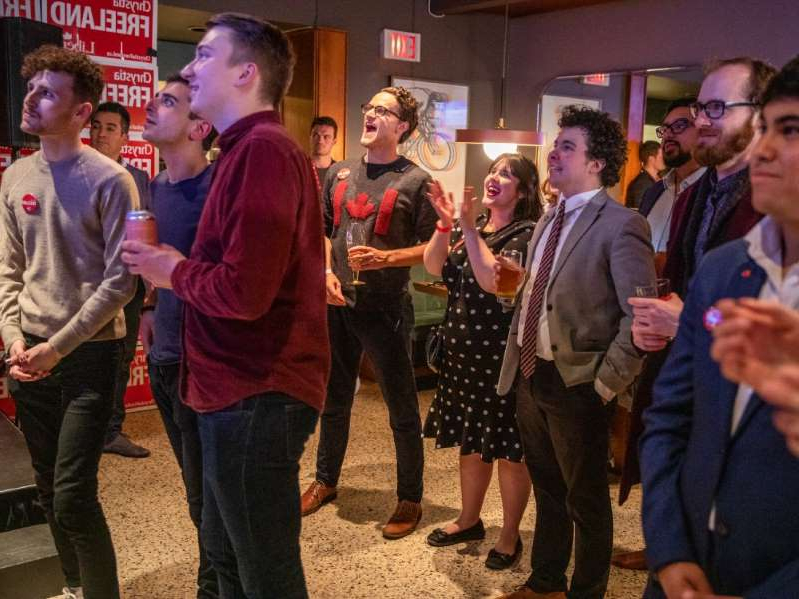 a group of people standing in front of a crowd posing for the camera: Liberal supporters cheer as election results begin to come in, at the closing party of Liberal incumbent candidate Chrystia Freeland, during Canada's 43rd general election, in Toronto, Ontario, Canada, at The Peacock Public House, October 21, 2019.