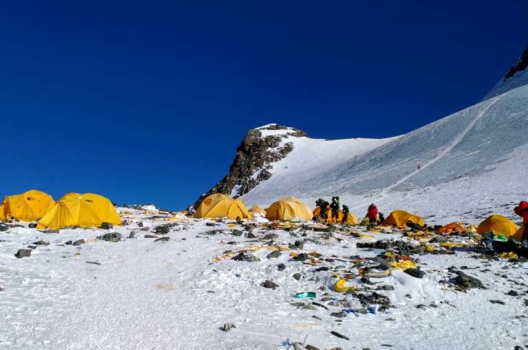 a group of people walking across a snow covered mountain: Mount Everest has been dubbed world's highest rubbish dump