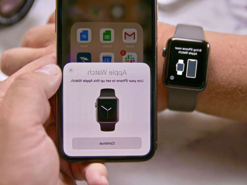 a hand holding a cellphone: We walk you through how to pair a new Apple Watch to your iPhone as well as unpair and erase your old one. John Kim/CNET