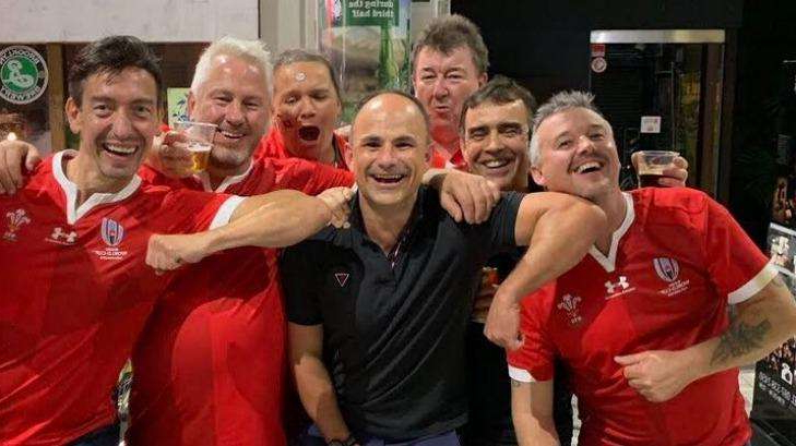Alexandre Debanne et al. posing for the camera: Referee Jaco Peyper (black shirt) has found himself in hot water after posing for this photo with Wales fans.