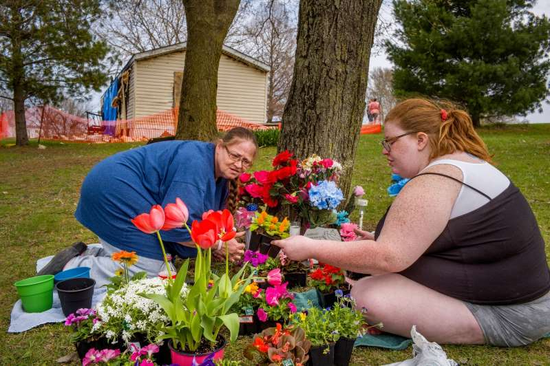 Nancy Parsons holding a flower garden: Katie Alwood, left, and her mother, Lori Alwood, plant flowers April 17, 2019 near the Goodfield mobile home, in background, where five relatives died in an April 6 fire. (David Zalaznik/Journal Star via AP)