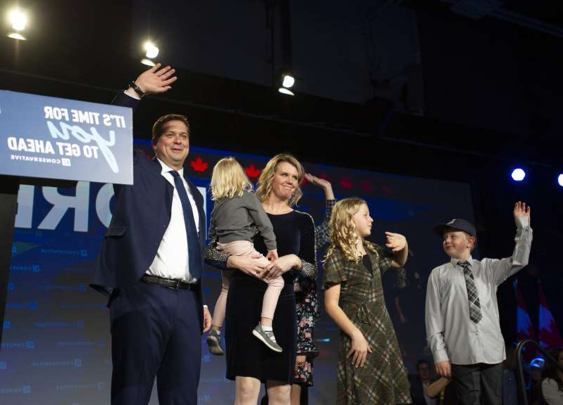 Nicole Brown, Andrew Scheer standing in front of a crowd posing for the camera: Scheer and his family wave to the crowd after his address at his Conservative campaign election night event in Regina. (Photograph by Mark Taylor)
