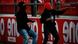 Olympiacos hooligans storm the pitch and attack Bayern Munich fans with sticks and fireworks at a YOUTH GAME in brutal bid to get it called off... before players finish the match with centre-circle kickabout!