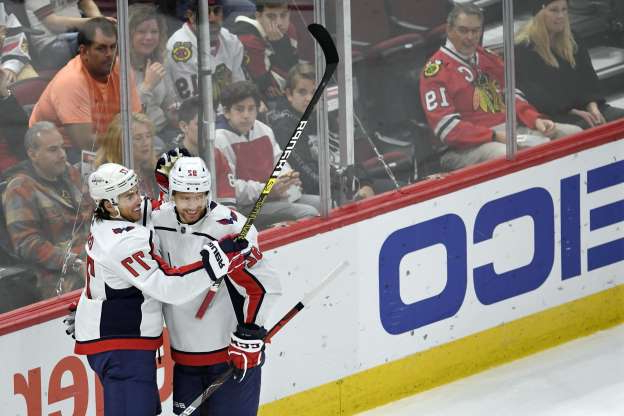 Washington Capitals' T.J. Oshie (77) celebrates with teammate Evgeny Kuznetsov (92), of Russia, after scoring a goal during the first period of an NHL hockey game against the Chicago Blackhawks, Sunday, Oct. 20, 2019, in Chicago. (AP Photo/Paul Beaty)