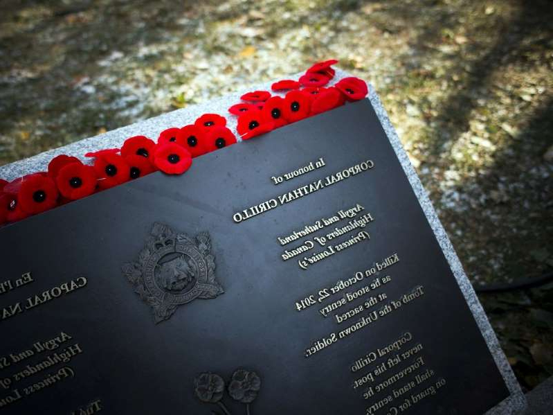 a black and red text: Poppies lay on the monument for Corporal Nathan Cirillo after the National Remembrance Day Ceremony at the National War Memorial in Ottawa on Saturday, November 11, 2017. Ashley Fraser/Postmedia
