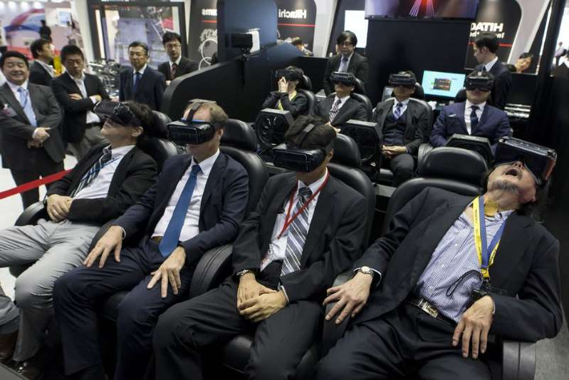 a group of people sitting in front of a crowd: VR exhibits were popular at the 2017 Tokyo Motor Show, and it's likely that won't change in 2019. The guy on the left seems really into it. Tomohiro Ohsumi/Getty Images