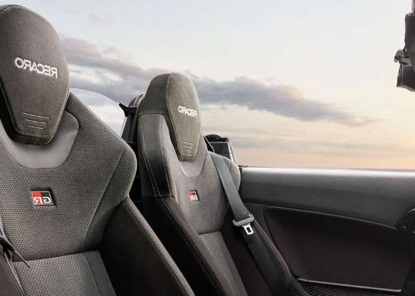 a person sitting in a car: Here's a nice shot of those body-hugging Recaro bucket seats.