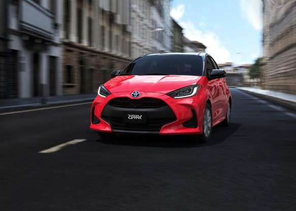 a red car driving down a street: For more photos of the 2020 Toyota Yaris, keep on clickin'!