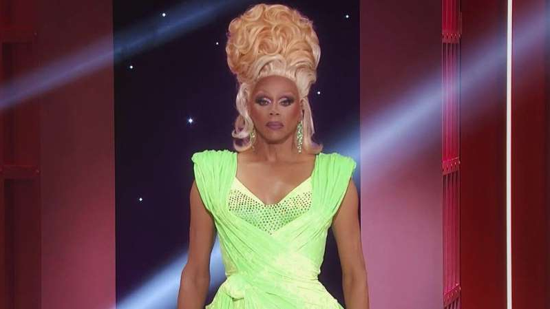 RuPaul in a yellow dress posing for the camera