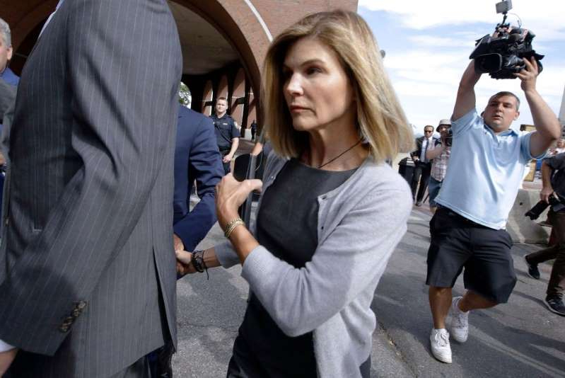 a group of people looking at a cell phone: Lori Loughlin departs federal court after a hearing in a nationwide college admissions bribery scandal on August 27, 2019 in Boston, Massachusetts.