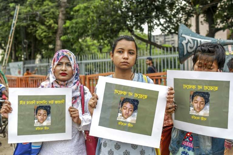 a group of people posing for a photo: Women hold pictures of murdered teenager Nusrat Jahan Rafi during a protest in Dhaka