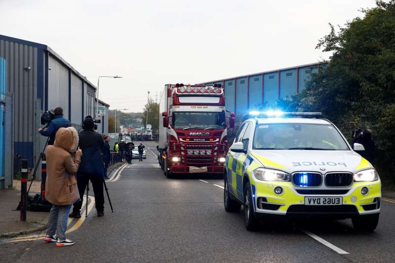 a group of people riding on the back of a truck: The scene where bodies were discovered in a lorry container, in Grays, Essex