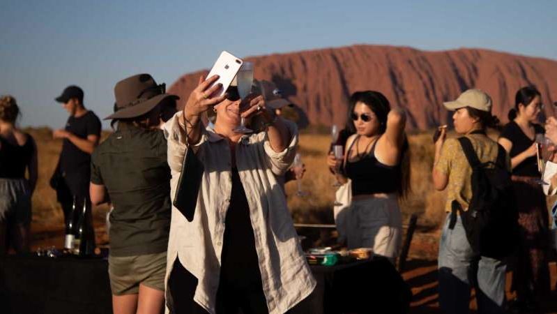 a group of people that are talking on a cell phone: Marie Masters said she had always wanted to see and climb Uluru. (ABC News: Samantha Jonsher)