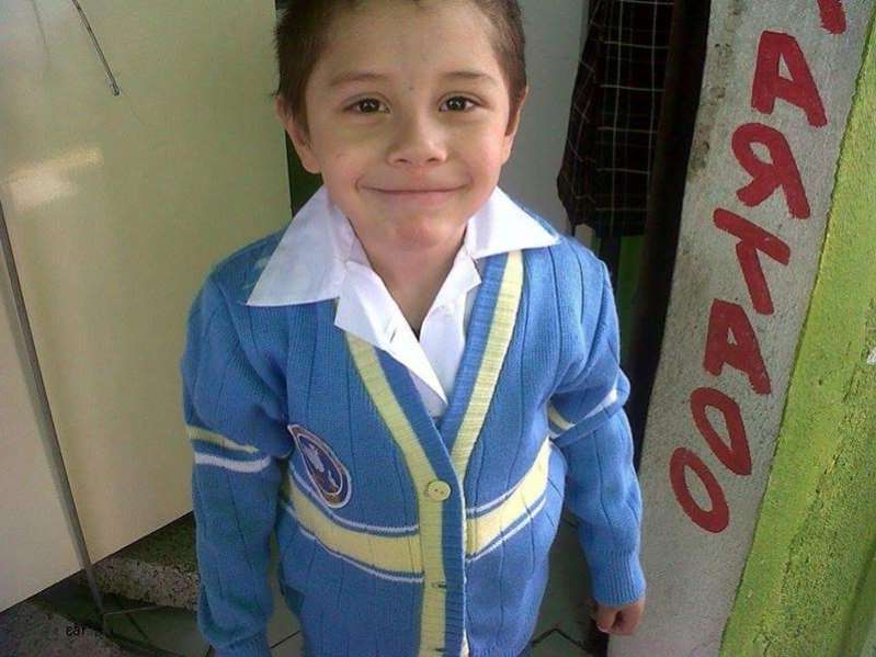 a young boy wearing a blue shirt and smiling at the camera