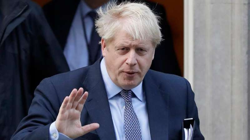 Boris Johnson wearing a suit and tie: British lawmakers back Prime Minister Boris Johnson's Brexit bill in principle but vote down his timetable, threatening October 31 deadline for U.K.'s exit from the European Union.