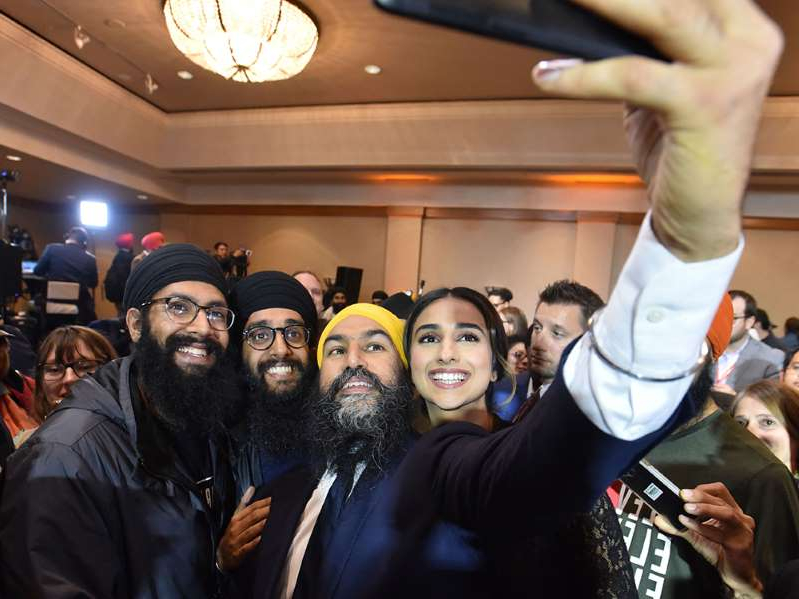 Jagmeet Singh et al. standing in front of a crowd: NDP Leader Jagmeet Singh and his wife, Gurkiran Kaur, take a selfie with supporters at an NDP election night party in Burnaby, B.C., on Oct. 21, 2019.