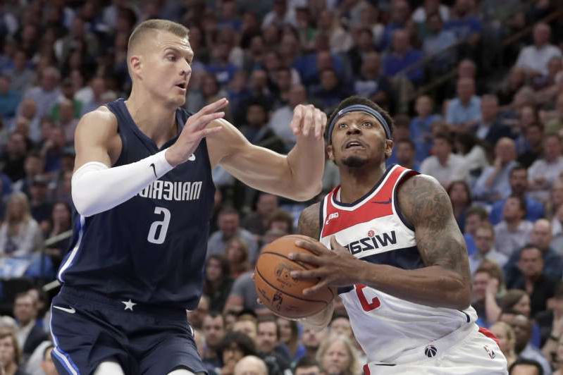Washington Wizards' Bradley Beal, left, heads to the basket as Dallas Mavericks' Kristaps Porzingis (6) defends during the first quarter of an NBA basketball game in Dallas, Wednesday, Oct. 23, 2019. (AP Photo/Tony Gutierrez)
