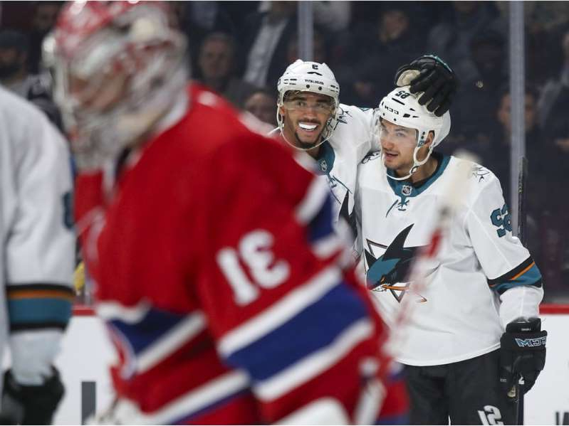a group of baseball players standing on top of a field: Canadiens goalie Carey Price skates away as Sharks' Kevin Labanc, left, is congratulated by team-mate Evander Kane after scoring goal during second period Thursday night at the Bell Centre.