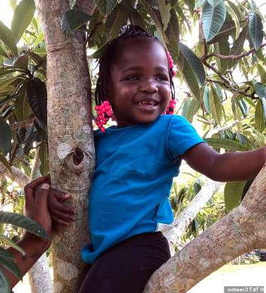 a little girl standing next to a tree: 'Since activation my family has been so excited, and everyone works on speech with Q'ela and makes sure she keeps her coil attached to her head,' said mum Nikitia