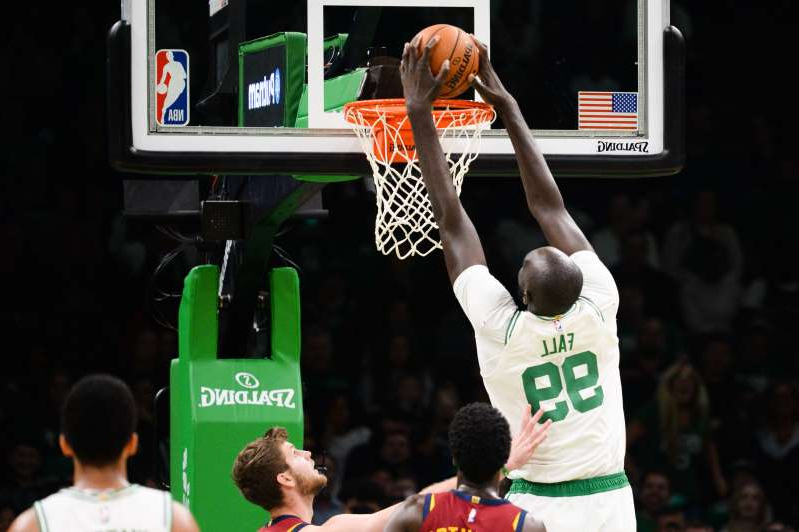 a man standing in front of a basketball game: BOSTON, MA - OCTOBER 13: Tacko Fall #99 of the Boston Celtics dunks the ball against the Cleveland Cavaliers in the fourth quarter at TD Garden on October 13, 2019 in Boston, Massachusetts. NOTE TO USER: User expressly acknowledges and agrees that, by downloading and or using this photograph, User is consenting to the terms and conditions of the Getty Images License Agreement. (Photo by Kathryn Riley/Getty Images)