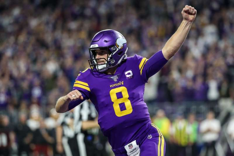 a man wearing a helmet: Minnesota Vikings quarterback Kirk Cousins (8) celebrates a touchdown run by running back Dalvin Cook (not pictured) during the second quarter against the Washington Redskins at U.S. Bank Stadium on October 24, 2019.