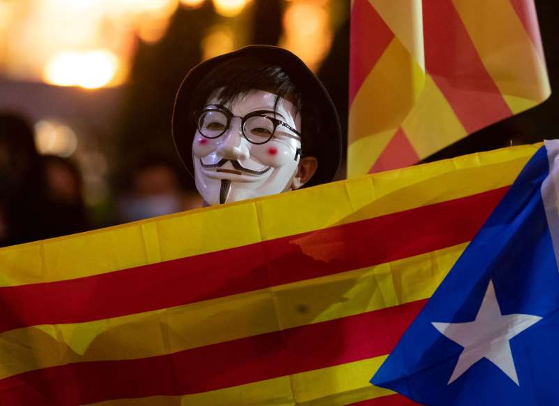 HONG KONG, CHINA - 2019/10/24: A Hong Kong masked protester holding a Catalonia flag during the demonstration. Hundreds of masked protesters gathered at Charter Garden in Central to show solidarity with demonstrators in Catalonia fighting for political freedom and in protest against sentences handed down to Catalonian politicians. (Photo by May James/SOPA Images/LightRocket via Getty Images)