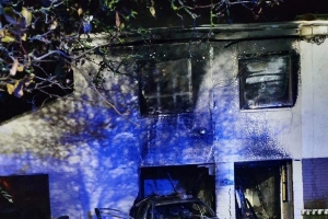 Investigation after car driven into vacant house and set on fire
