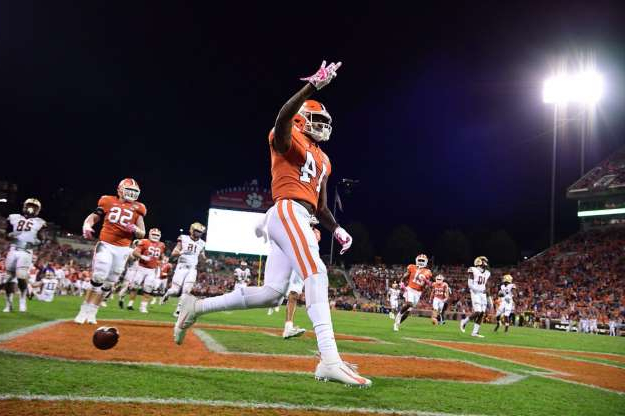 a baseball player taking a swing at a ball: Clemson wide receiver Diondre Overton (14) holds up three fingers — one finger for each touchdown he scored against Boston College on Saturday, Oct. 26, 2019.