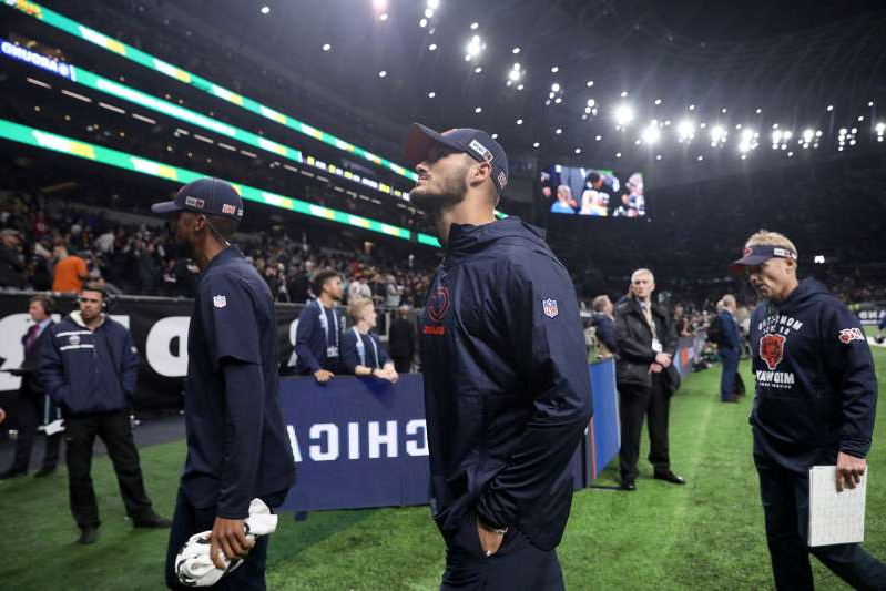 a group of people standing in front of a crowd: Injured Chicago Bears quarterback Mitch Trubisky walks to the locker room after a loss to the Oakland Raiders Sunday, Oct. 6, 2019 at Tottenham Hotspur Stadium in London, England.
