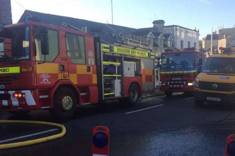 a bus that is parked on the side of a road: Firefighters responded to the fire in Balbriggan on Saturday