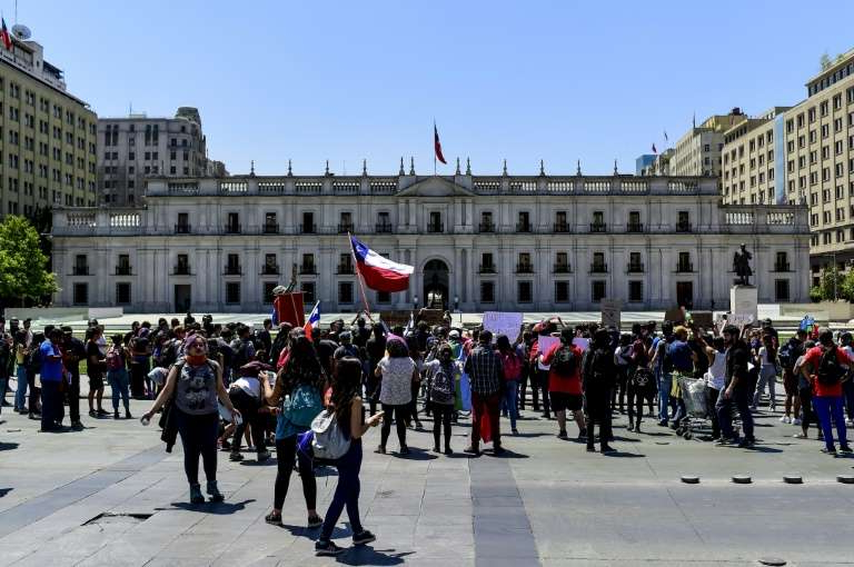 a group of people walking in front of a building: Demonstrators outside the Presidential Palace, known as La Moneda, in Santiago, Chile where President Sebastian Pinera shuffled his cabinet amid a crisis