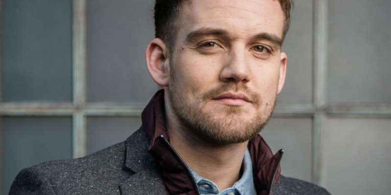 a man wearing a suit and tie smiling and looking at the camera: Coronation Street's Ali Neeson and Gary Windass have a showdown next week as they clash over Maria Connor.