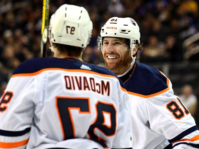 a close up of James Neal in a baseball game: NEW YORK, NEW YORK - OCTOBER 12: James Neal #18 and Connor McDavid #97 of the Edmonton Oilers talk during the third period against the New York Rangers at Madison Square Garden on October 12, 2019 in New York City.