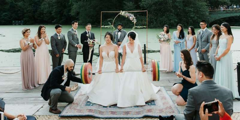 a group of people around each other: Two Brooklyn brides did a tandem deadlift during their wedding ceremony. Photographer Eileen Meny captured the moment the couple lifted the barbell together.