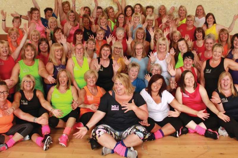a group of people posing for a photo: Members of Airdrie dance fitness class Lost in Music have made a charity calendar to raise funds for Maggie's Lanarkshire and Breast Cancer Now