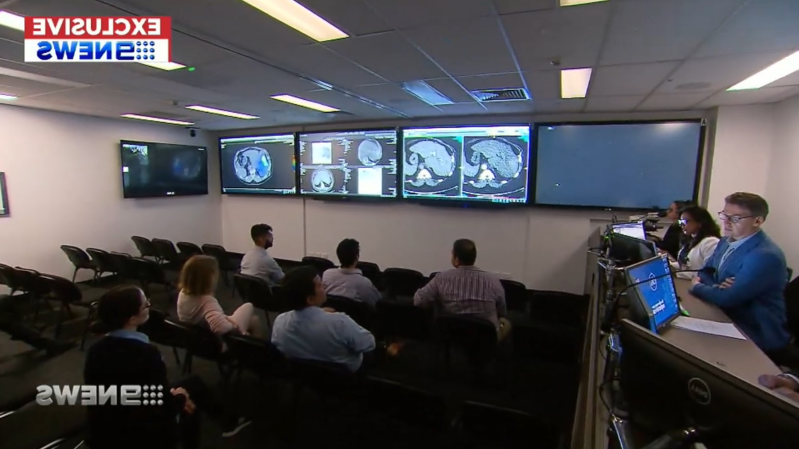 a group of people sitting in front of a television: The new $700,000 facility enables doctors to bring in an expert from anywhere in the world via video conference.