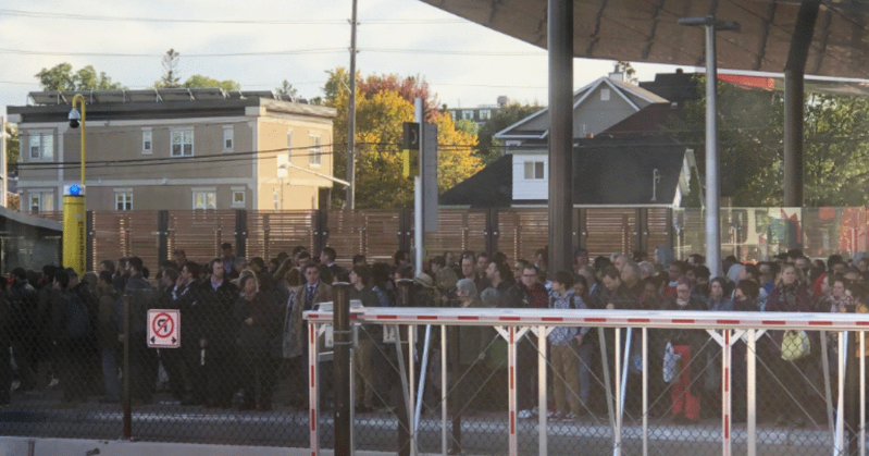 a group of people standing next to a fence