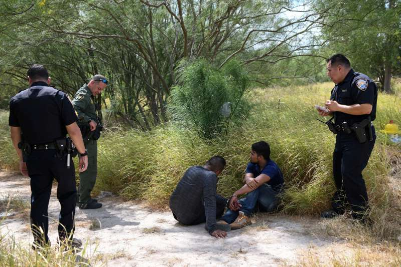 a group of people standing next to a tree: FILE PHOTO: Migrant men sit on the ground after being detained by law enforcement for illegally crossing the Rio Grande and attempting to evade capture in Hidalgo
