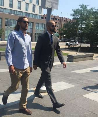 a man wearing a suit and tie walking down the street: Michael Theriault, left, a Toronto police constable, and Christian Theriault, a civilian, arrive at court on August 2019.