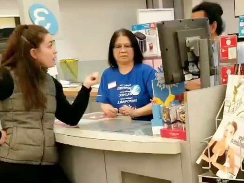 a person standing in a room: A customer at a Burnaby Shoppers Drug Mart berates staff for speaking Chinese.