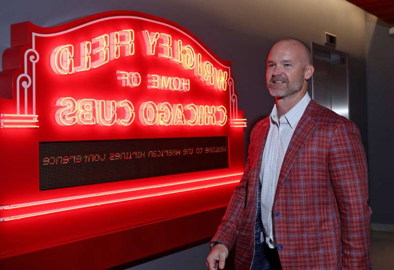 David Ross wearing a red jacket standing in front of a sign: The Cubs introduced David Ross as the 55th manager in franchise history on Oct. 28, 2019.