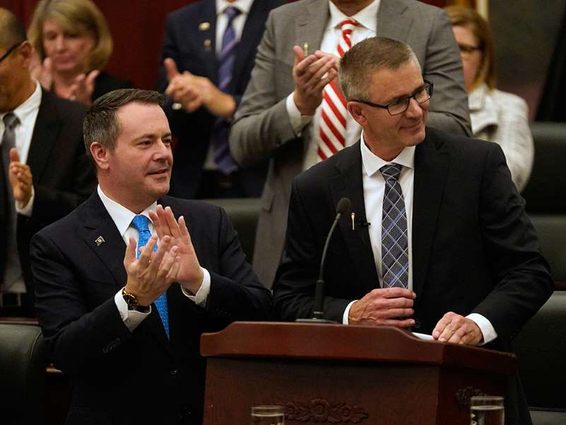 Jason Kenney wearing a suit and tie standing in front of a crowd: Alberta Finance Minister Travis Toews, left, is applauded by Premier Jason Kenney after Toews delivered his budget at the Alberta Legislature in Edmonton on Oct. 24, 2019.