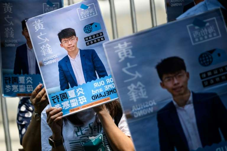 Joshua Wong, Joshua Wong are posing for a picture: Posters of pro-democracy activist Joshua Wong are placed in front of the Central Government Complex as he announced in September his run for District Council elections in Hong Kong