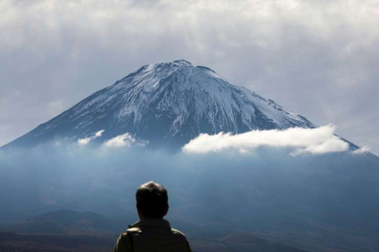 a man standing in front of a mountain: Experts warn that climbing Mount Fuji outside of the official season is dangerous, though it is not prohibited