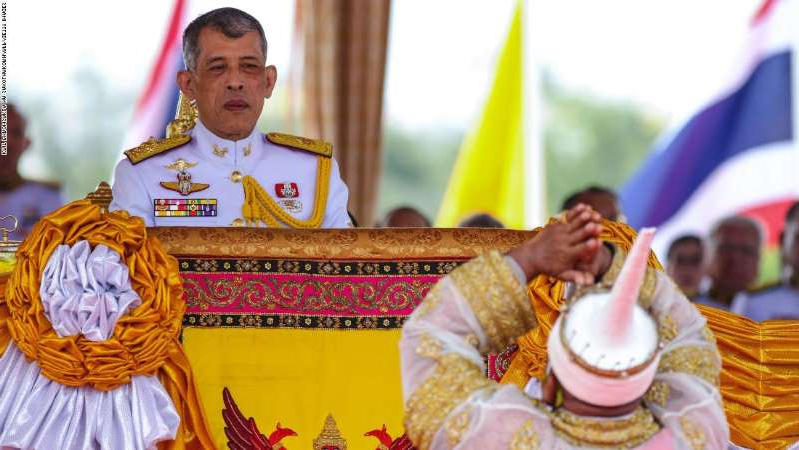 a person sitting at a table with a cake: Thailand's King Maha Vajiralongkorn (R) presides the annual royal ploughing ceremony near the Grand Palace in Bangkok on May 9, 2019. (Photo by Krit Phromsakla Na SAKOLNAKORN / THAI NEWS PIX / AFP)        (Photo credit should read KRIT PHROMSAKLA NA SAKOLNAKORN/AFP/Getty Images)