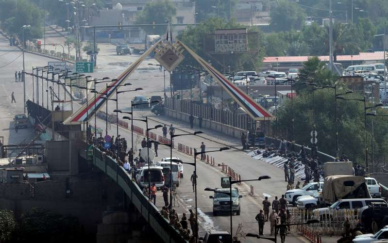 Security forces fire tear gas and close the bridge leading to the Green Zone during a demonstration in Baghdad, Iraq, Wednesday, Oct. 30, 2019. Anti-government protests in Iraq gained momentum Wednesday with tens of thousands of people gathered in a central square in Baghdad and across much of the country's Shiite-majority central southern provinces. (AP Photo/Hadi Mizban)