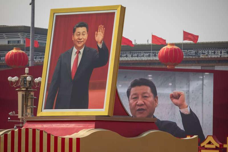 Xi Jinping standing in front of a mirror posing for the camera: A float carrying a portrait of Chinese President Xi Jinping, moves past Tiananmen Square in Beijing, during a military parade marking the 70th anniversary of the founding of the People's Republic of China.
