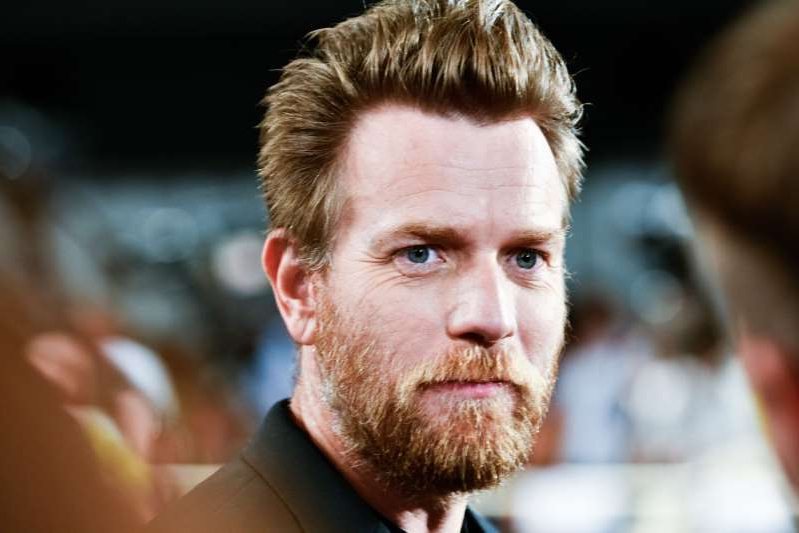 a close up of Ewan McGregor with a beard looking at the camera