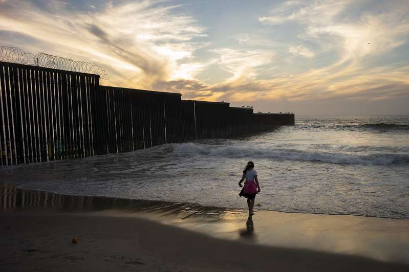 a person walking across a beach next to a body of water: A border wall separates San Diego from Tijuana, Mexico.