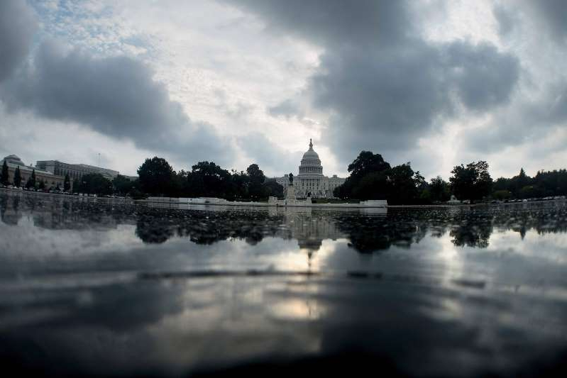 clouds in the sky over a body of water: Image: The U.S. Capitol building in Washington